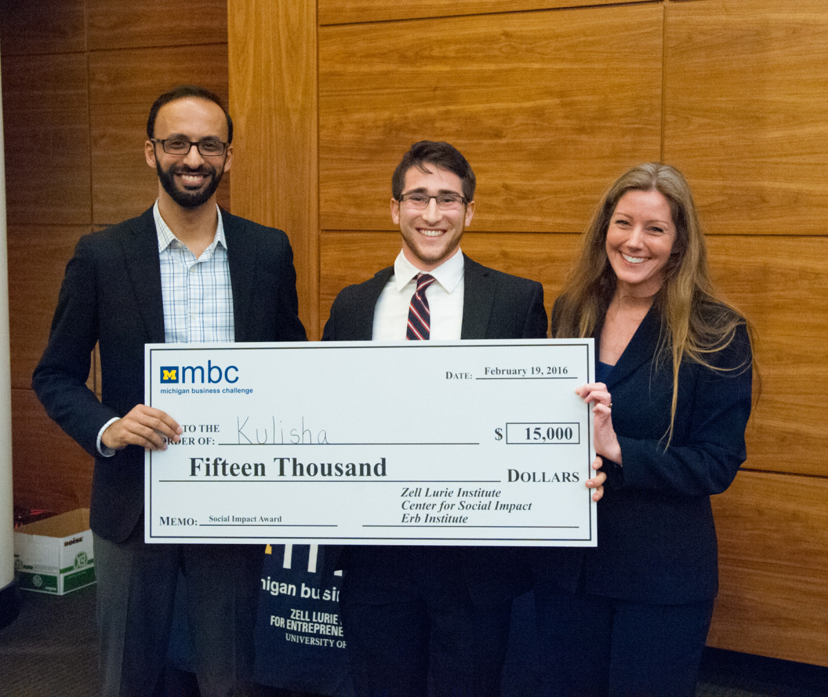 "Three smiling people hold large check that reads, ""Pay to the order of: Kulisha, $15,000 Fifteen Thousand Dollars, Memo: National Impact Award, Zell Lurie Institute, Center for Social Impact, Erb Institute."""