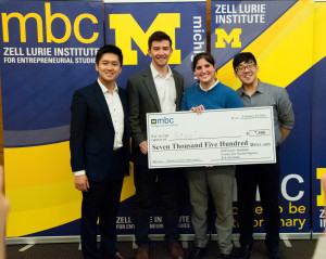 "Four smiling MBC contestants holding large check that reads, ""Pay to the order of: StepFor, $7,500 Seven Thousand Five Hundred Dollars, Zell Lurie Institute, Center for Social Impact, Erb Institute."""