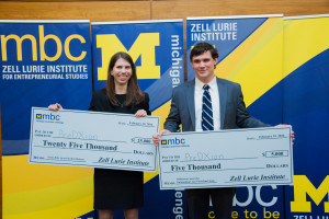 "Two smiling Michigan Business Challenge contestants holding two large checks. The check in the young woman on the left's hands reads, ""Pay to the order of PreDXion, $25,000 Twenty Five Thousand Dollars, Zell Lurie Institute."" The check in the young man on the right's hands reads, ""Pay to the order of: PreDXion, $5,000 Five Thousand, Zell Lurie Institute."""