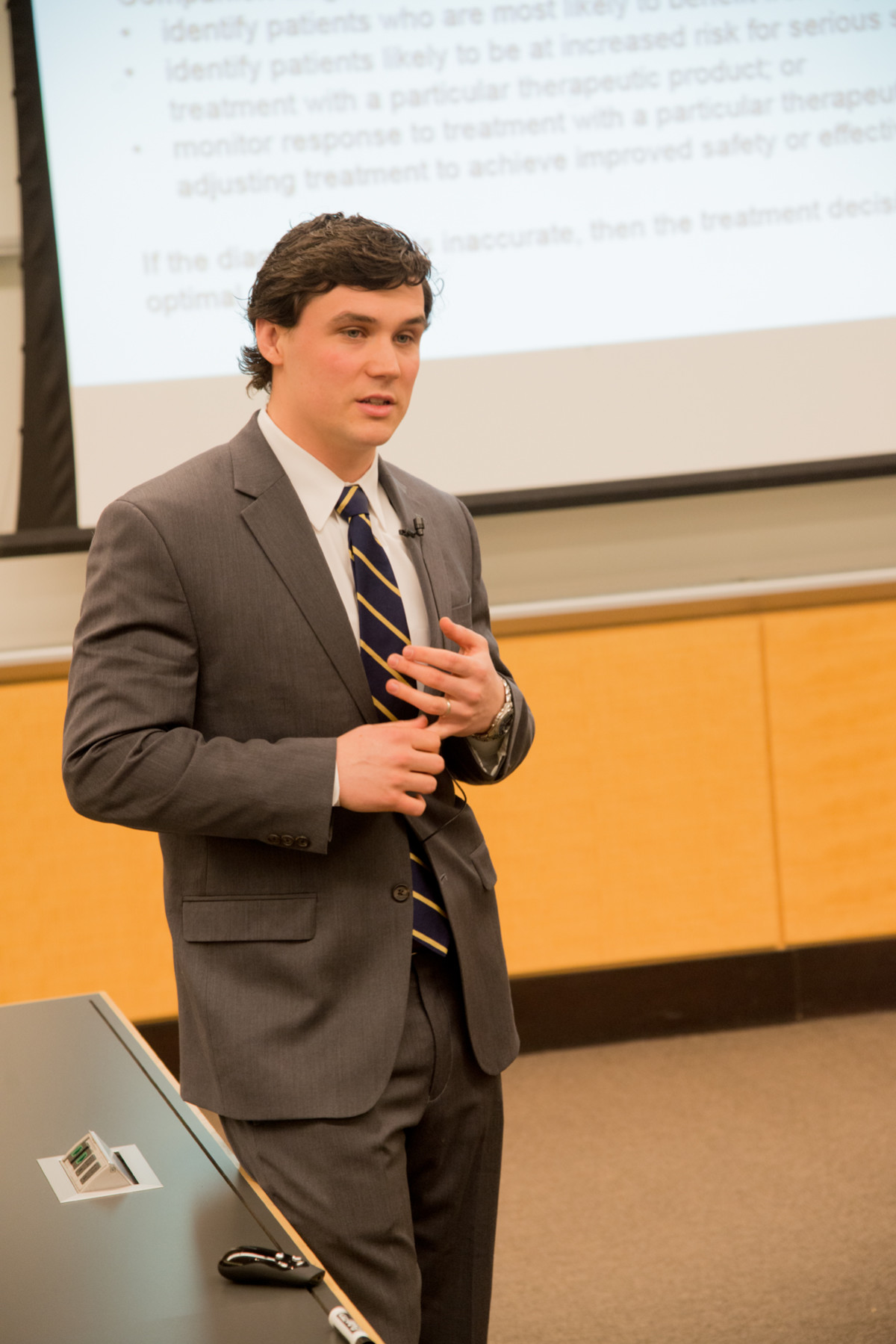 Ross School of Business student standing in front of projector screen during his presentation.