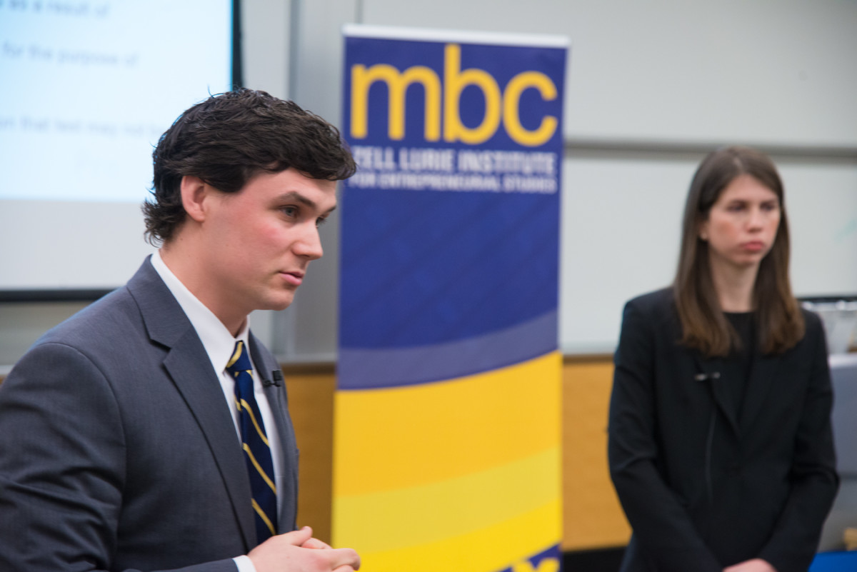 Serious, well-dressed Ross Business School student stands to the left of the Michigan Business Challenge logo with hands folded in front of him