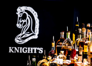 Knight's horse head logo to the left of a large selection of alcohol.