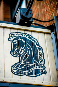 Close-up of Knight's Restaurant's horse head logo on wooden sign.